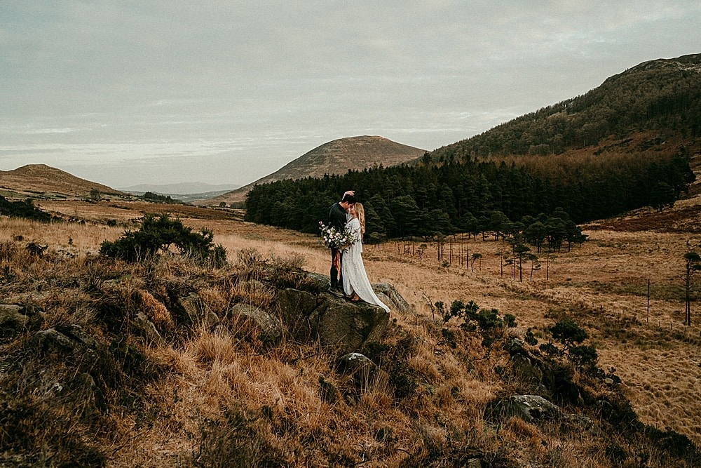 A portrait of a bride & groom in the Mourne Mountains in Northern Ireland. Boho wedding dress. Adventure