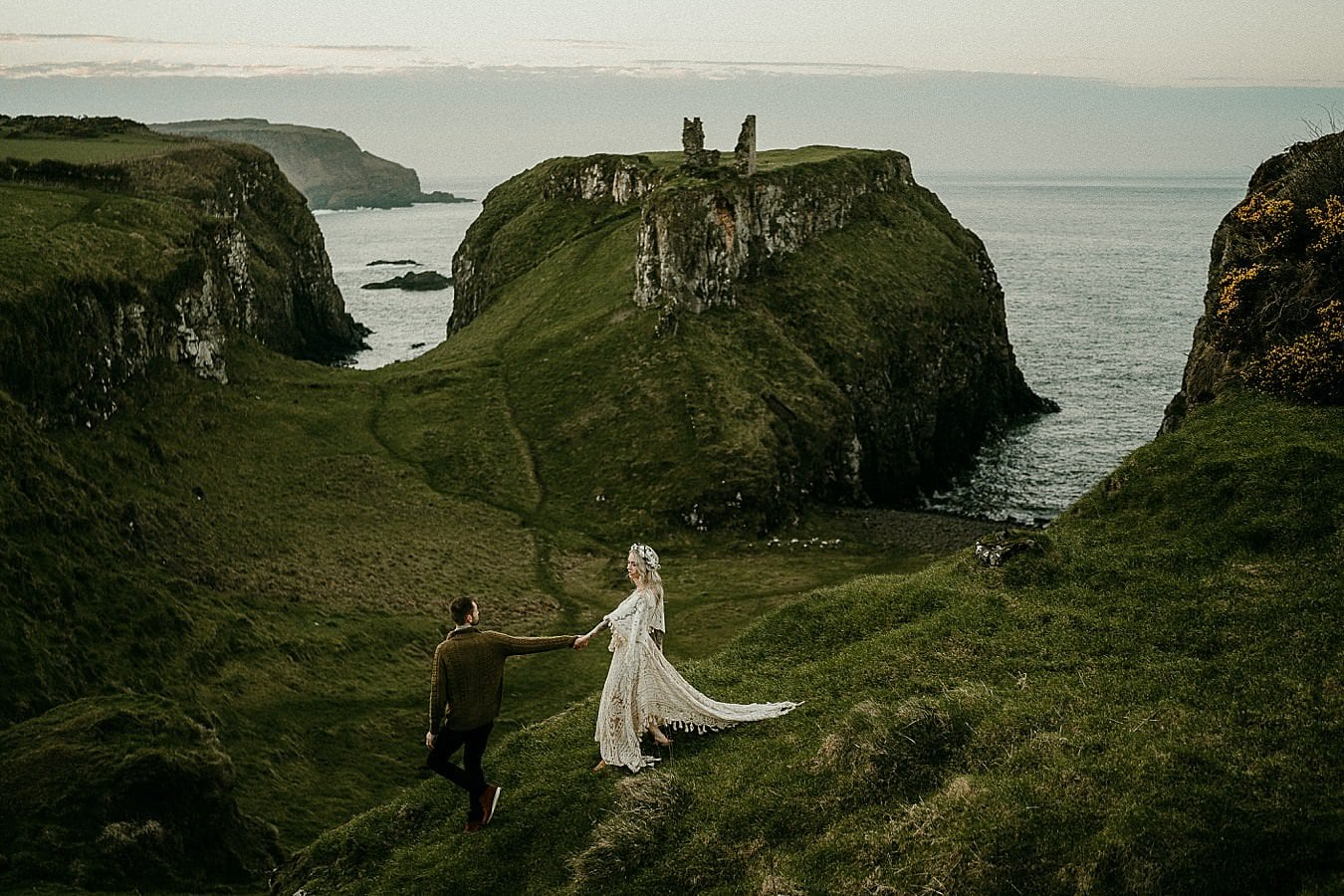 A sunset portrait in beautiful light on the Causeway Coast. Romantic adventure elopements in Europe. Dunseverick Castle.